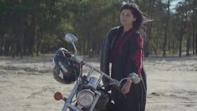 Dziewczyna patrzeje w kamerę przed sosnowym lasowym hobby z czarni włosy pozycją przy motocyklem, podróżuje zbiory wideo