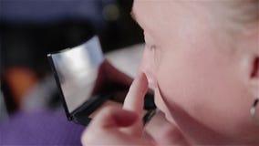 Dziewczyna patrzeje w małym lustrze który trzyma w jego wręcza stawia dalej jej twarzy makeup Ładny boczny widok zbiory wideo