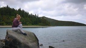 Dziewczyna patrzeje w smartphone na tle jeziora i jezioro ma zabawę zbiory wideo