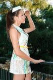 Dziewczyna patrzeje z someone w modnej papier sukni stoi z ręką jej czoło zdjęcia royalty free