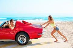 Dziewczyna pcha łamanego samochód na plażowym śmiesznym facecie Zdjęcia Royalty Free