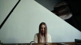 Dziewczyna pianista bawi? si? muzyk? na pianinie na tle ?ciana w zwolnionym tempie zbiory wideo