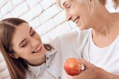 Dziewczyna pielęgnuje starszej kobiety w domu Obejmują Kobieta trzyma jabłka obraz stock