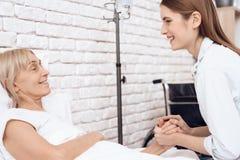 Dziewczyna pielęgnuje starszej kobiety w domu Trzymają ręki, śmia się obraz royalty free