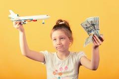 Dziewczyna, pieniądze, utrzymanie dolary i samolot w rękach, podróży pojęcie obrazy royalty free