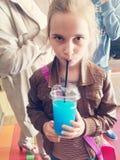 Dziewczyna pije błękitnego zimnego napój Fotografia Royalty Free