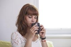 Dziewczyna pije filiżankę herbata zdjęcie stock