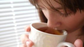 Dziewczyna pije gorącej herbaty z plasterkiem cytryny obsiadanie na windowsill przy okno i ono uśmiecha się zbiory
