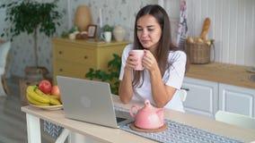 Dziewczyna pije kawę, ogląda film na laptopie, cieszy się ranek w domu, zwolnione tempo zdjęcie wideo