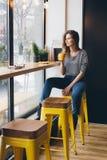 Dziewczyna pije kawę w sklep z kawą Obrazy Royalty Free