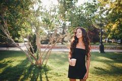 Dziewczyna pije kawę w parku Zdjęcia Royalty Free