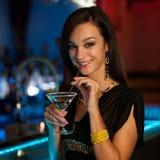 Dziewczyna pije koktajl w noc klubie Obrazy Stock
