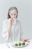 Dziewczyna pije mleko i ma lunch przy stołem Obrazy Royalty Free