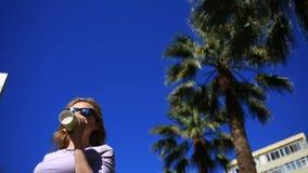 Dziewczyna pije napój na ulicie od rozporządzalnej filiżanki przeciw drzewkom palmowym i niebieskiemu niebu Dolny widok zbiory wideo