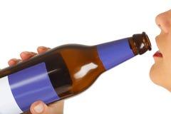 Dziewczyna pije piwo kobieta wręcza mienie butelkę piwo Fotografia Stock