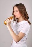 Dziewczyna pije pomarańczowy świeżego z bliska Biały tło Fotografia Royalty Free
