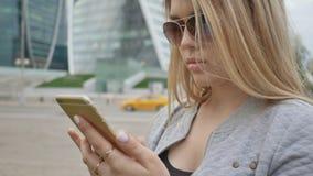 Dziewczyna pisać na maszynie na telefonie przeciw tłu wieżowowie w centrum miasto zdjęcie wideo