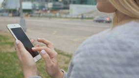 Dziewczyna pisać na maszynie na telefonie przeciw tłu wieżowowie w centrum miasto zbiory