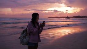Dziewczyna pisać na maszynie wiadomość blisko oceanu przy zmierzchem zbiory wideo