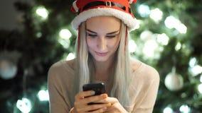 Dziewczyna pisać na telefonie i ono uśmiecha się na bożych narodzeniach zbiory