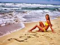 Dziewczyna pisać w piasku 2017 blisko oceanu z fala Fotografia Royalty Free