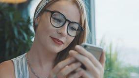 Dziewczyna pisze chłopak na smartphone i ono uśmiecha się Kobieta używa gona na telefonie komórkowym w kawiarni zdjęcie wideo