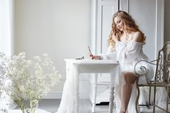 Dziewczyna pisze liście jej ukochany mężczyzna, siedzi w domu przy stołem w sukni, czystości i niewinności światła białego, blond Obrazy Stock