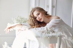 Dziewczyna pisze liście jej ukochany mężczyzna, siedzi w domu przy stołem w sukni, czystości i niewinności światła białego, blond Obraz Stock