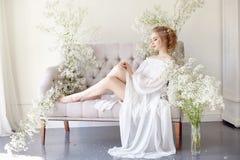 Dziewczyna pisze liście jej ukochany mężczyzna, siedzi w domu przy stołem w sukni, czystości i niewinności światła białego, blond Zdjęcie Royalty Free