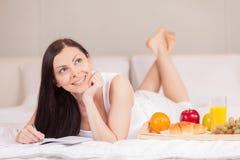 Dziewczyna pisze mieć śniadanie w łóżku w ranku Zdjęcia Royalty Free