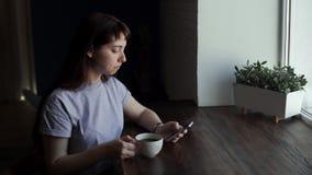 Dziewczyna pisze na telefonie i pi? przy kawiarni? blisko okno herbata lub kawa zbiory