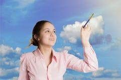 Dziewczyna pisze w niebie z muśnięciem obraz royalty free