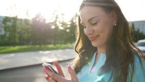 Dziewczyna pisze wiadomości na smartphone i ono uśmiecha się zbiory