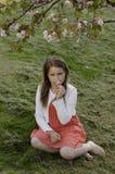 Dziewczyna pod kwitnącym drzewem nad zielonej trawy tłem Fotografia Royalty Free