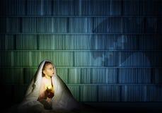 Dziewczyna pod pokrywami z latarką Obraz Royalty Free
