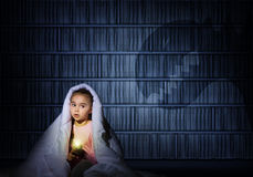 Dziewczyna pod pokrywami z latarką Zdjęcie Stock