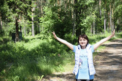 Dziewczyna podnosi jej ręki niebo w pogodnym lato lesie fotografia stock
