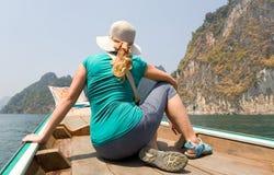 Dziewczyna podróżnika spojrzenia przy egzotyczną wyspą podczas gdy siedzący w łodzi obrazy stock