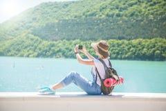 Dziewczyna podróżnik robi selfi z smartphone na halnym jeziorze Robi fotografii dla podróż blogu Widok od plecy turysta t zdjęcie stock