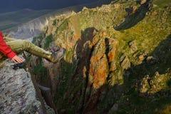 Dziewczyna podróżnik siedzi na krawędzi falezy Żeńscy cieki w półdupkach obrazy royalty free