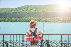 Dziewczyna podróżnik z akci kamerą na halnej jeziornej dziewczynie bierze fotografię dla podróż blogu widoku od plecy turystyczny fotografia stock