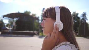 Dziewczyna podr??uje spacery wzd?u? miasto ulicy z he?mofonami, s?ucha muzyka i ono u?miecha si? dziewczyna w bia?ej sukni z d?ug zbiory wideo