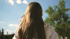 dziewczyna podr??uje w mie?cie, s?ucha muzyka przeciw niebieskiemu niebu i chmurnieje Dziewczyna chodzi wzd?u? miasto ulicy z zbiory wideo