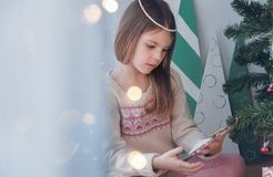 Dziewczyna podziwia Bożenarodzeniową zabawkę na choince obrazy stock