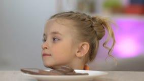 Dziewczyna pojawiać się spod stołowego i kraść kawałka czekoladowy bar, ząb zdjęcie wideo