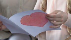 Dziewczyna pokazuje babci handmade kartka z pozdrowieniami z sercem, rodzinna miłość, opieka zbiory