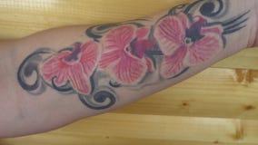 Dziewczyna pokazuje kamerze tatuaż orchidee na ręce zbiory wideo