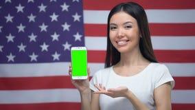 Dziewczyna pokazuje smartphone z zieleń ekranem, USA flaga na tle, tłumacza app zdjęcie wideo