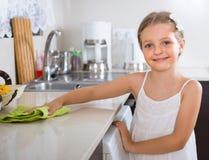 Dziewczyna poleruje stołowego wierzchołek w domu Obrazy Stock