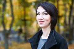Dziewczyna portret, kolor żółty opuszcza na tle, jesieni miasta park, sezon jesienny, czerń żakiet Zdjęcie Stock